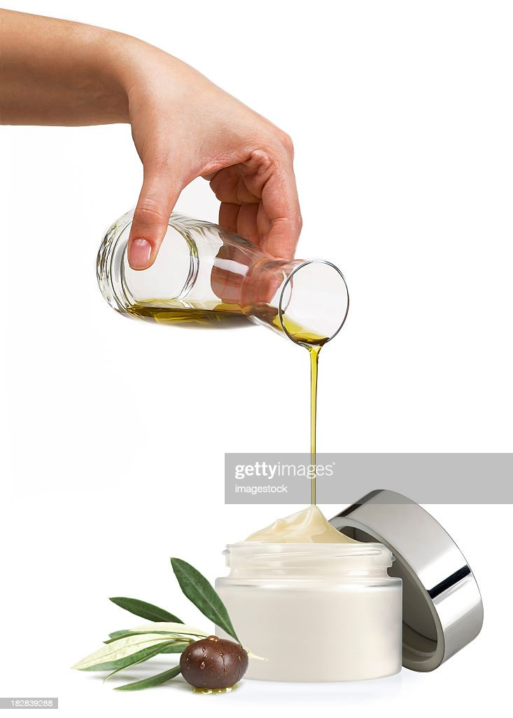 A pot of face cream having olive oil poured into it : Stock Photo