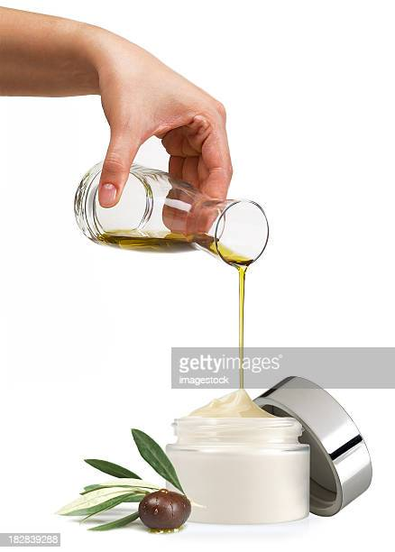 A pot of face cream having olive oil poured into it