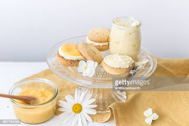 Pot of homemade lemon curd with melting moment biscuits and lemon buttercream