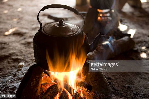 A pot of the local Akha tea brews over an open fire in the guest lodge built to house trekkers just outside the Ban Nam Lai Akha village The Akha are...