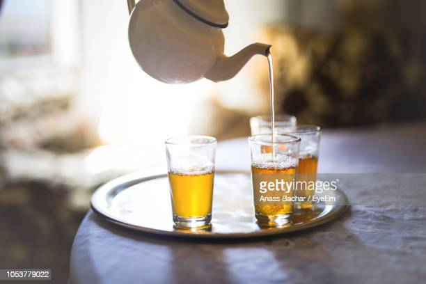 Pot Pouring Tea In Glass On Table