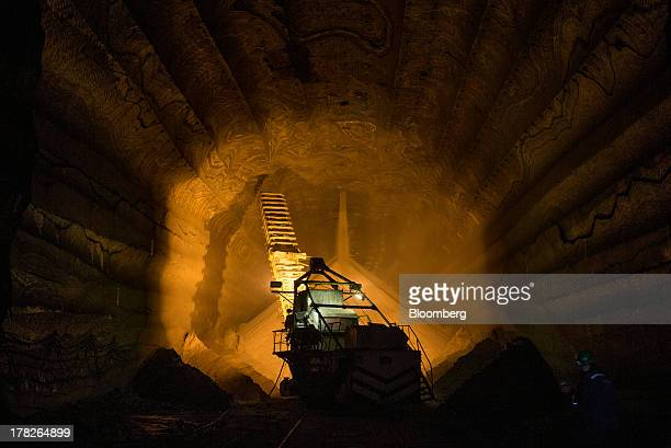 Potash falls from a hole in the rock wall into a storage area inside the potash mine operated by OAO Uralkali in Berezniki Russia on Saturday Aug 24...