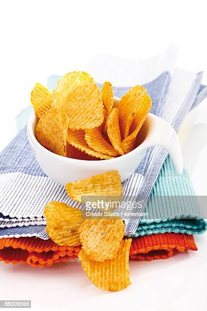 Cup of potato chilli chips on place mat, close-up