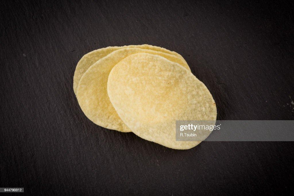 Potato chips on a black : Stock Photo