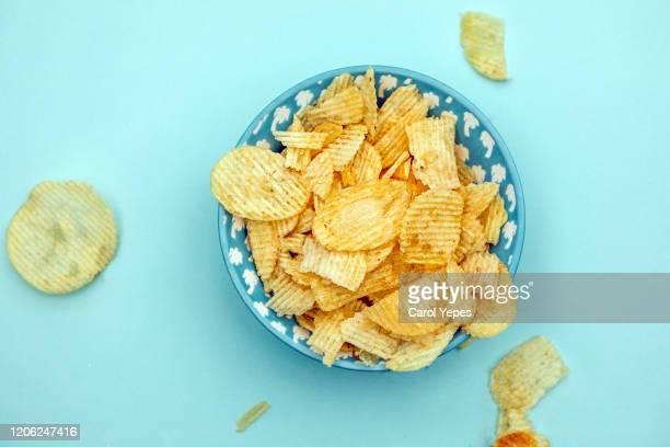 potato chips top view.turqoise background - ポテトチップス ストックフォトと画像