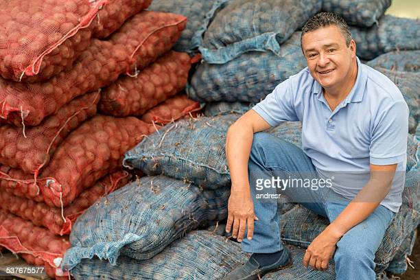 Potato farmer sitting on packages at the farm