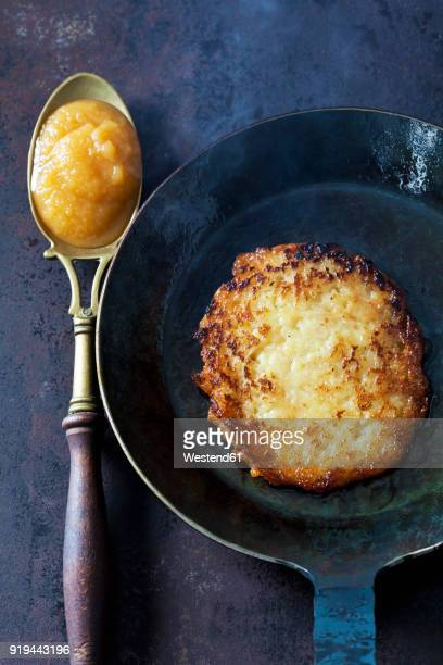 Potato fritter in frying pan and spoon of apple sauce