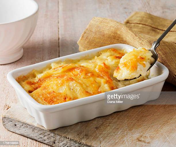 Potato gratin in white serving dish with metal spoon