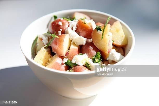 Potato salad with goat cheese in white bowl