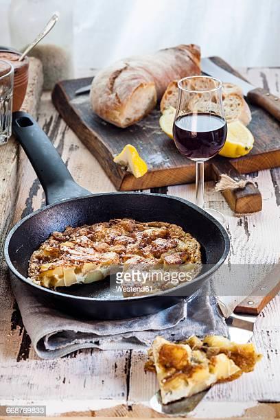 Potato tortilla in pan, port wine and bread