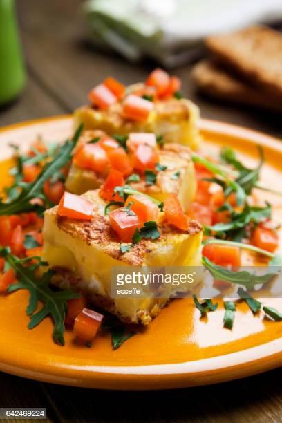 Potato tortilla prepared with arugula and tomatoes pieces