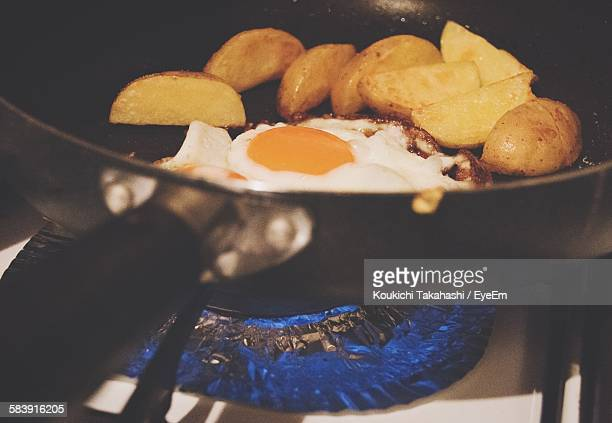 Potatoes And Fried Egg In Cooking Pan On Gas Burner