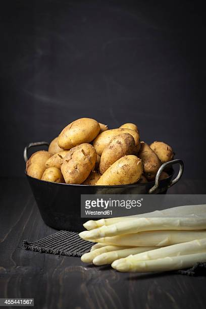 Potatoes and white asparagus on table, close up