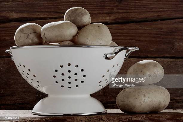potatoes (solanum tuberosum) in a kitchen sieve - colander stock photos and pictures