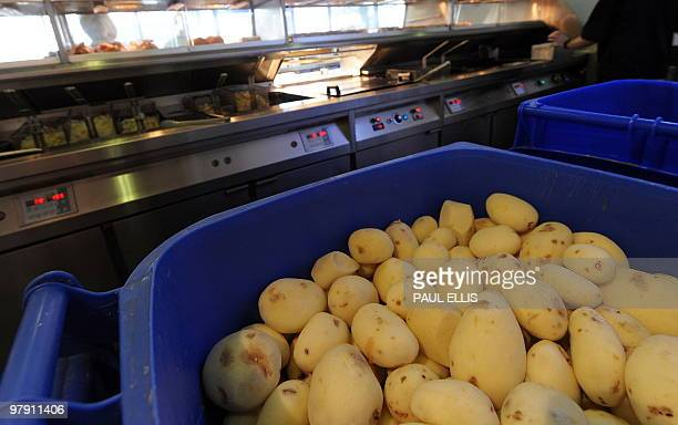 Potatos are prepared for frying at a Fish and Chip Takeaway in Manchester northwest England on March 10 2010 Whether wrapped in newspaper and eaten...