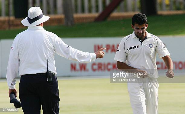 A cricket umpire makes a remark to India's bowler Zaheer Khan after the ball that he bowled to South African batsman Paul Adams hit him 09 December...