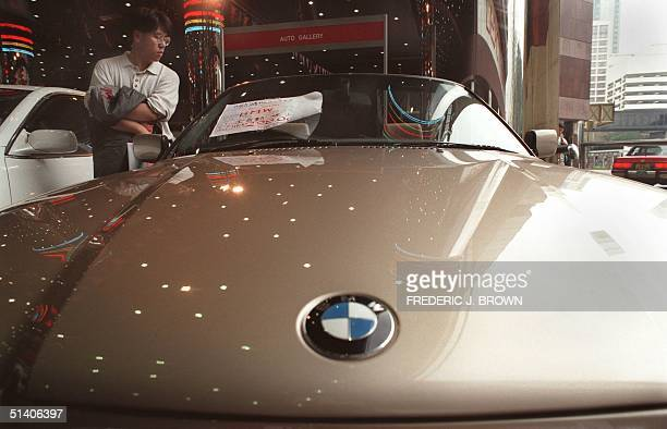 A potential buyer looks at the interior of a 1994 BMW 325i at a secondhand car sale in Hong Kong 14 February The asking price for this convertible...