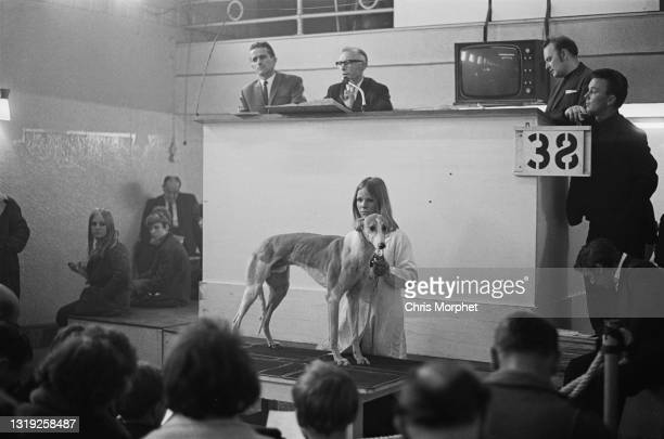 Potential buyers examining a Greyhound dog for sale at Hackney Racetrack, London, UK, 10th April 1968.