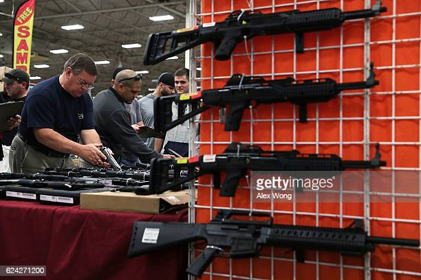 Potential buyers try out guns which are displayed on an exhibitor's table during the Nation's Gun Show on November 18 2016 at Dulles Expo Center in...