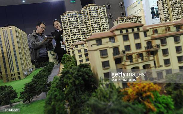 Potential Chinese real estate investors view property for sale at the Overseas and China Property Expo in Beijing on April 5 2012 Home prices in...