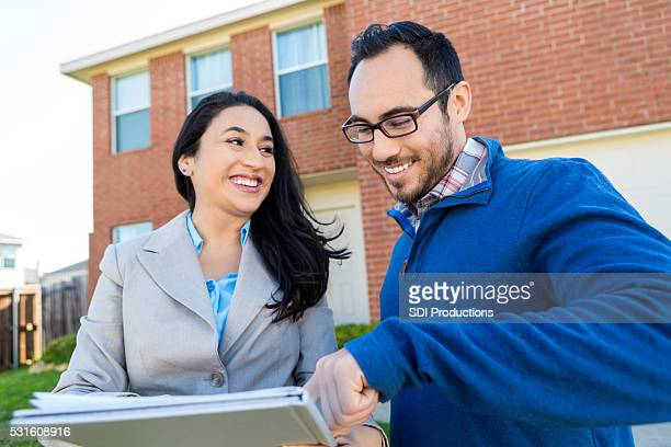 potential client discusses home with realtor - brick house stock pictures, royalty-free photos & images