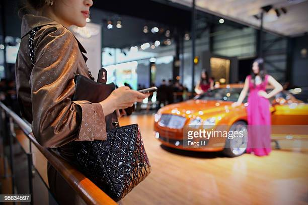 A potential consumer stands beside a Bentley car during a special media opening of the Beijing Auto Show on April 23 2010 in Beijing of China Major...