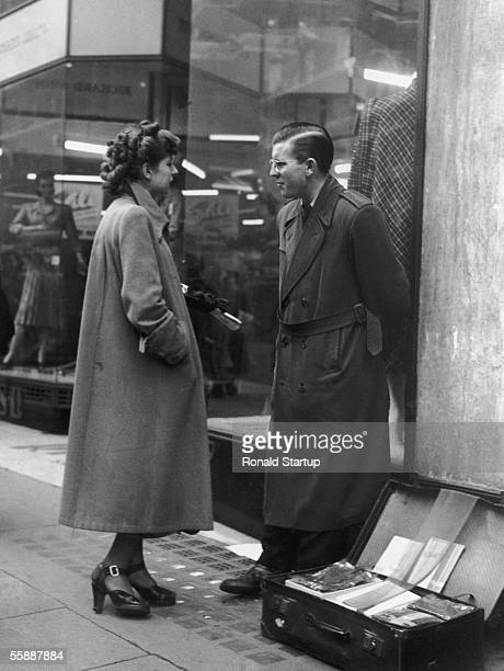 A potential customer approaches a street trader illegally selling nylon stockings from a suitcase on Oxford Street London 10th February 1951 Original...