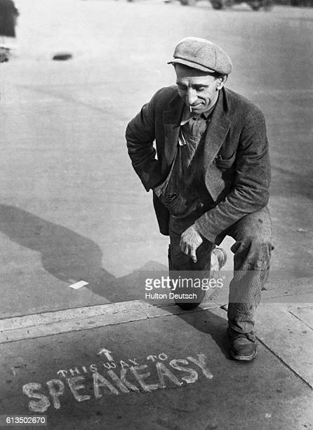 A potential customer examining an enterprising advertisement for an illegal drinking den or speakeasy during US Prohibition in the 1920s