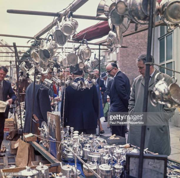 Potential customers and browsers view a collection of silverware and silver plate objects on display for sale at an open air antiques stall on...