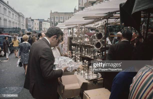 Potential customers and browsers view a collection of silverware and silver plate objects for sale on display at an open air antiques stall on...