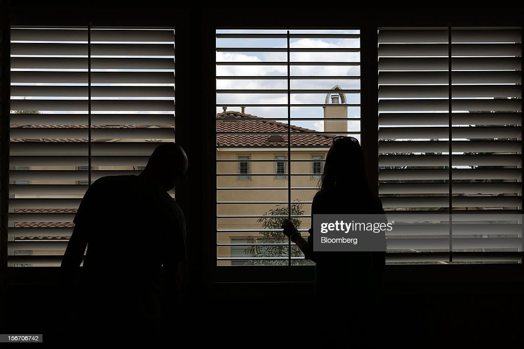 Potential house buyers Brandon Coughlin, left, and wife Kristina Coughlin look at the window blinds of a model home at the Van Daele Estates at Etiwanda development in Rancho Cucamonga, California, U.S., on Sunday, Nov. 18, 2012. The U.S. Census Bureau is scheduled to release housing starts figures on Nov. 20. Photographer: Patrick T. Fallon/Bloomberg via Getty Images