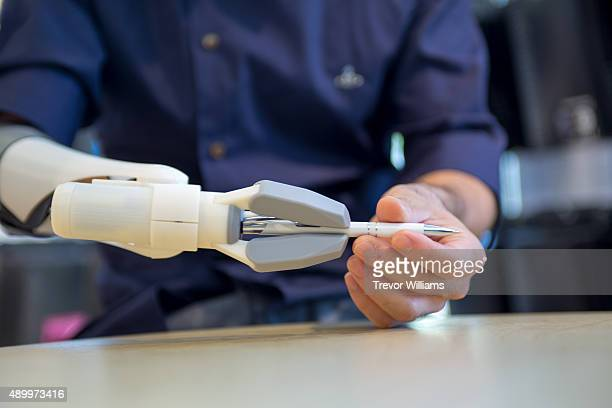 A potential user using his own muscles to open and close the pinch mechanism on this 3D printed prosthetic arm checks the practicality by attempting...