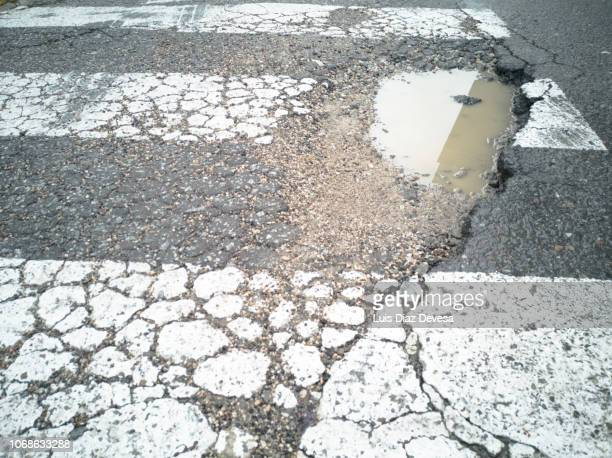 a pothole in the middle of the zebra crossing - pothole stock photos and pictures