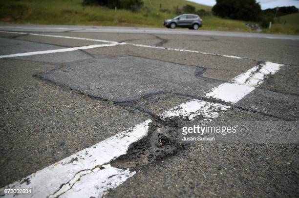 A pothole is visible on a road on April 25 2017 in San Rafael California According to an analysis brief commissioned by the nonprofit nonpartisan...