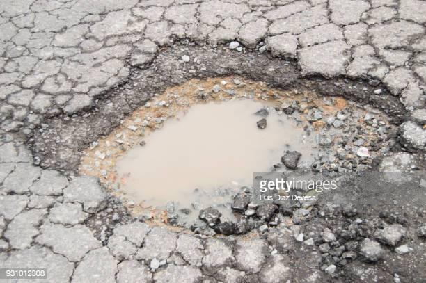 a pothole - vernieling stockfoto's en -beelden