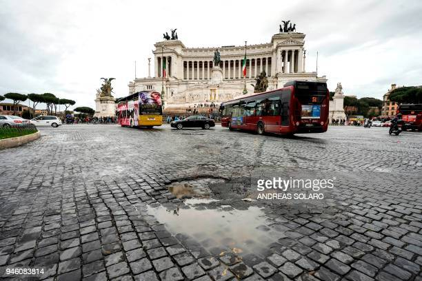 Potholes in cobblestones are pictured on Piazza Venezia in front of the Altare della Patria the unknown soldier monument in downtown Rome on April 12...
