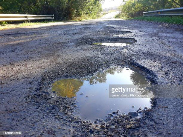 potholes in the middle of a mountain road - puddle stock pictures, royalty-free photos & images