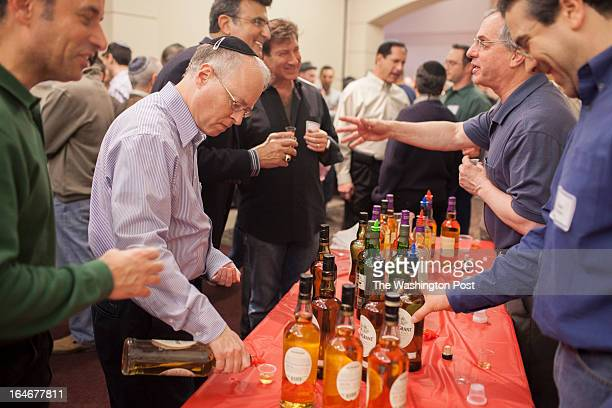 Geoffrey Berman pours a sample of a scotch during the third annual BBQ Scotch and Seder Summit held at Beth Sholom the largest Modern Orthodox...