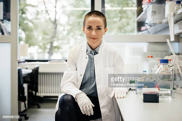 potrait of a female scientist sitting - laborkittel stock-fotos und bilder