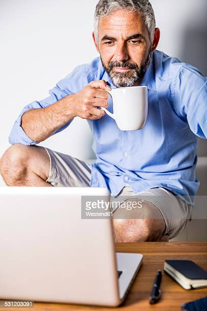 Potrait of businessman having a coffee break at his home office