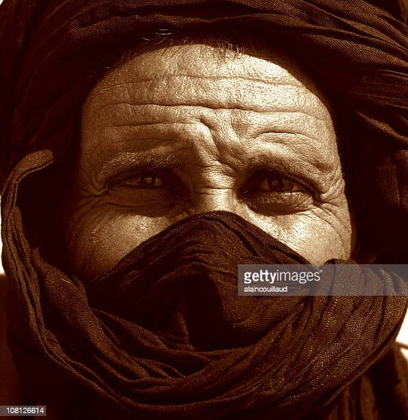 potrait of man's face wearing tuareg, sepia toned - tuareg tribe stock pictures, royalty-free photos & images
