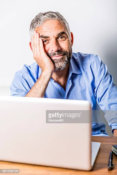 Potrait of smiling businessman with laptop at his home office