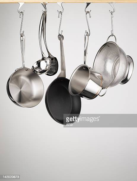 pots and pans hanging from hooks - cooking utensil stock photos and pictures