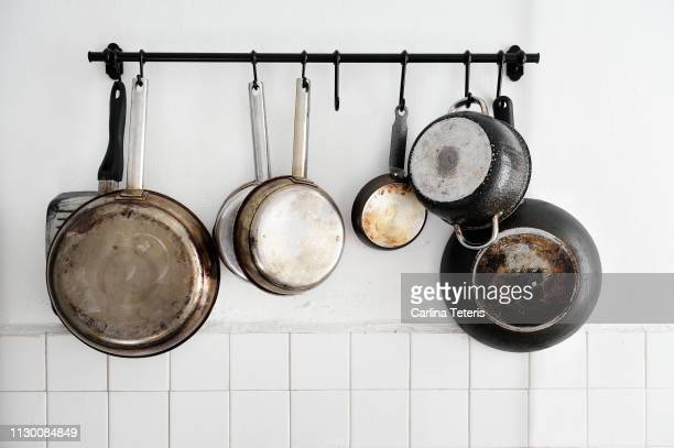 pots and pans hanging on a kitchen wall - cooking pan stock pictures, royalty-free photos & images