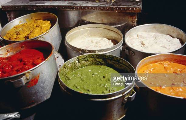 Pots in a restaurant containing colourfully spiced food.