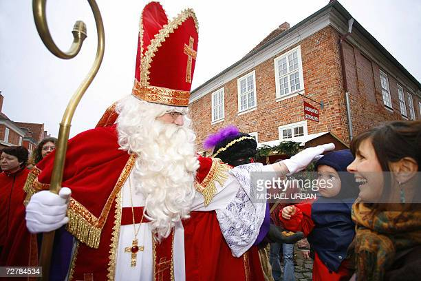 Sinterklaas and his Zwarte Pieten talk to residents as they visit the Dutch Quarter of Potsdam eastern Germany 09 December 2006 According to the...