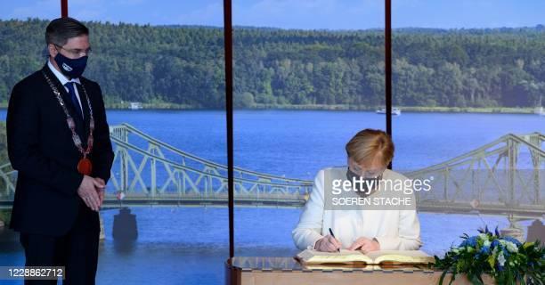 Potsdam Mayor Mike Schubert watches as German Chancellor Angela Merkel signs the Golden Book of the city of Potsdam following celebrations marking...