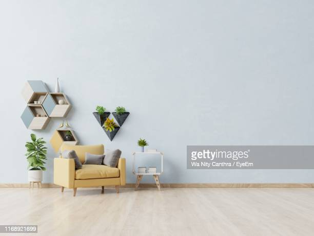 potted plant by sofa against white wall at home - hausdekor stock-fotos und bilder