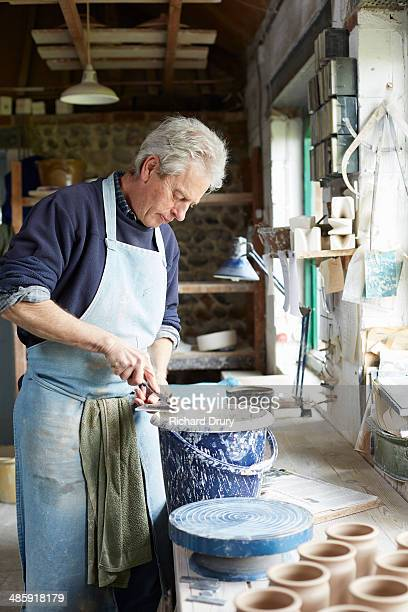 potter cleaning throwing batts - richard drury stock pictures, royalty-free photos & images