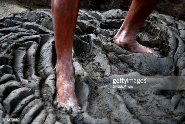Potter crushing soil by his feet, Jodhpur, Rajasthan, India, Asia